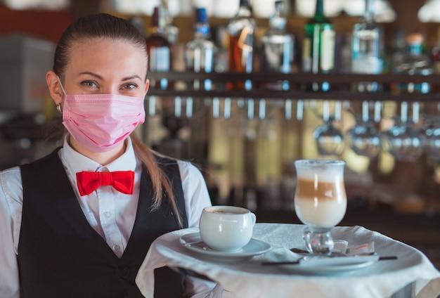 Официант работает в ресторане в медицинской маске.