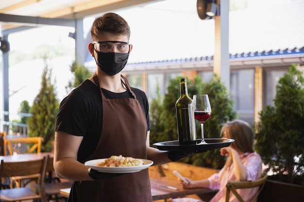Waiter works in a restaurant in a medical mask, gloves during coronavirus pandemic