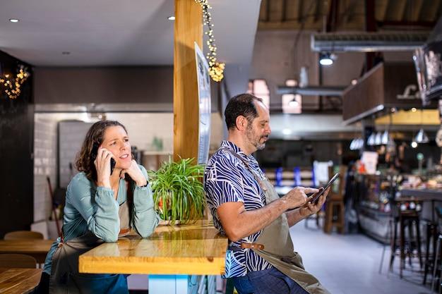 Официанты в кафетерии с помощью мобильного телефона и планшета