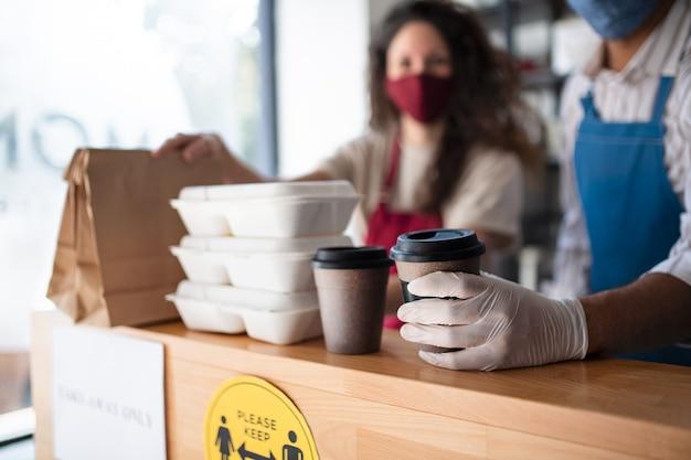 코로나바이러스 컨셉인 커피숍에서 테이크 아웃 주문을 준비하는 웨이터.