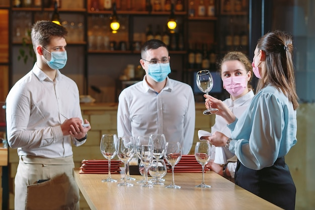The waiters of the restaurant in a medical mask learns to distinguish between the glasses.