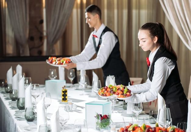 ゲストを迎える準備をしているレストランのテーブルで給仕をするウェイター。