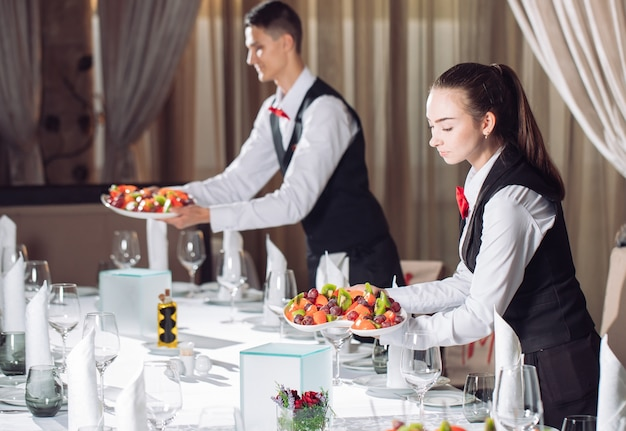 Waiters serving table in the restaurant preparing to receive guests.