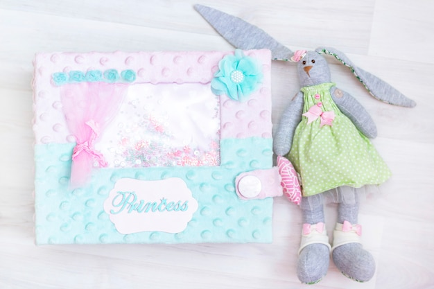 Waiting for the baby. girl. girl bunny toy, princess box on a light wooden background.