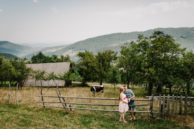 Waiting baby. happy family. pregnant woman, beloved husband stand holding hand on the grass. round belly. parenthood. the sincere tender moments. mountains, forests, nature, old house, cow, nine month