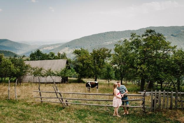 В ожидании ребенка. счастливая семья. беременная женщина, любимый муж стоять, держась за руку на траве. круглый живот. родительство. искренние нежные моменты. горы, леса, природа, старый дом, корова, девять месяцев