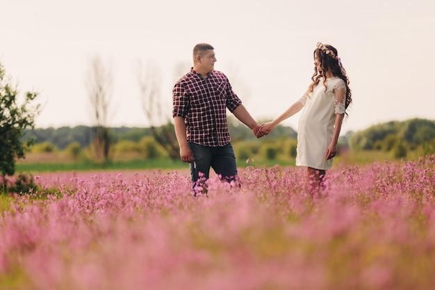 待っている赤ちゃん。親子関係。妊娠中の若い女性と彼女の夫は、ピンクの花のフィールドの屋外で幸せに行く