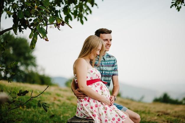 В ожидании ребенка. беременная женщина с любимым мужем сидят на скамейке возле дерева. муж обнимает круглый живот жены. родительство. искренние нежные моменты. горы, леса, природа, трава, поле.