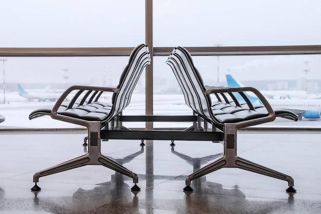 Кресла ожидания в зоне вылета аэропорта на фоне большого окна с видом на взлетное поле.