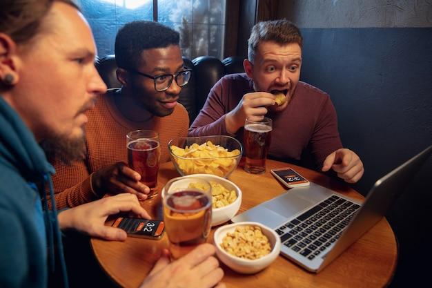 Ожидающий. взволнованные фанаты в баре с пивом и мобильным приложением для ставок, забивают на своих устройствах. экран с результатами матча, эмоциональные аплодисменты друзей. азартные игры, спорт, финансы, концепция современных технологий.
