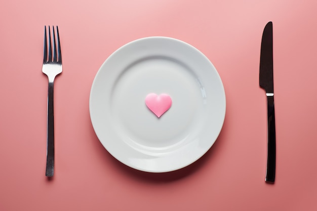 Waiting for a favorite dish in restaurant or cafe. heart on plate with fork and knife. lovers meeting at a daily lunch.