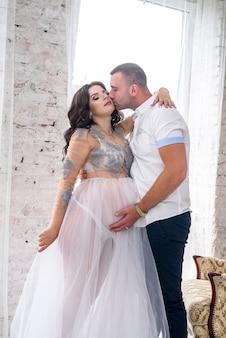 赤ちゃんを待っています。スタジオでポーズをとる素晴らしいペアの夫と妊娠中の妻