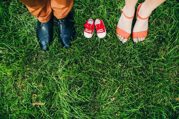 奇跡を待つ。大人と子供のための靴。両親の足の間の芝生の上に子供の靴。
