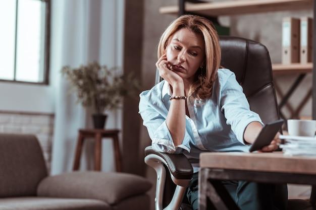電話を待っています。金髪で成功した賢い弁護士は、夫からの電話を待って悲しんでいる
