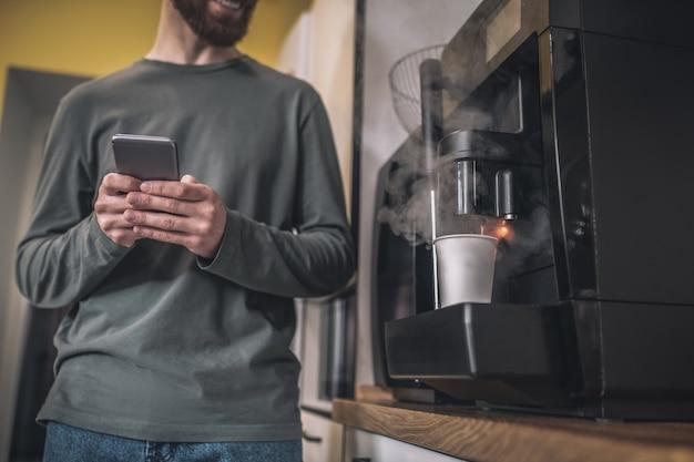 Жду кофе. человек с телефоном в руках, стоящий возле кофеварки
