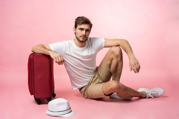 フライトを待っています。スーツケースと床に座っている男の旅行者。