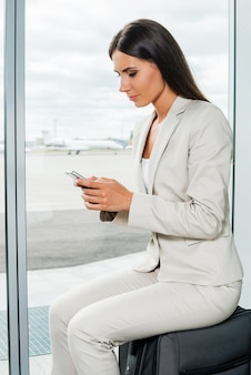 그녀의 비행을 기다리고 있습니다. 휴대전화를 들고 공항에서 비행기를 배경으로 가방에 앉아 그것을 바라보는 정장 차림의 젊은 여성 사업가의 측면
