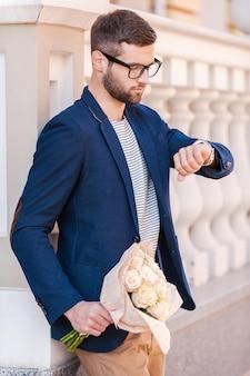 彼女を待っている。花の花束を保持し、通りに立っている間彼の時計を見ているスマートカジュアルウェアのハンサムな若い男