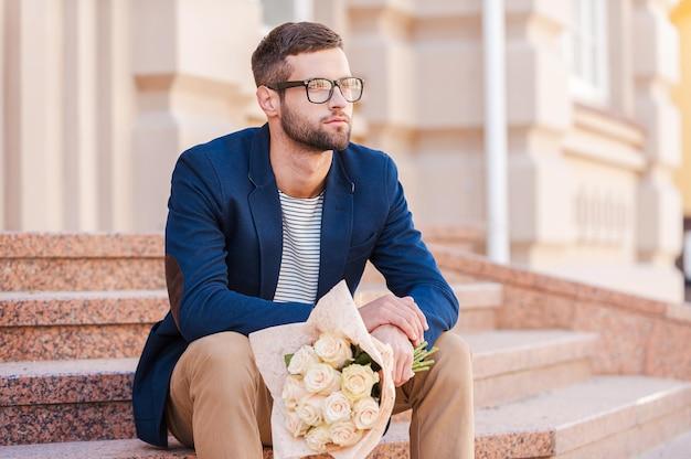 彼女を待っている。花の花束を保持し、家の近くの階段に座って目をそらすスマートジャケットのハンサムな若い男
