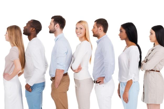 彼女の番を待っています。カメラを見て、他の人と並んで、白い背景に立って笑っている美しい若い女性の側面図