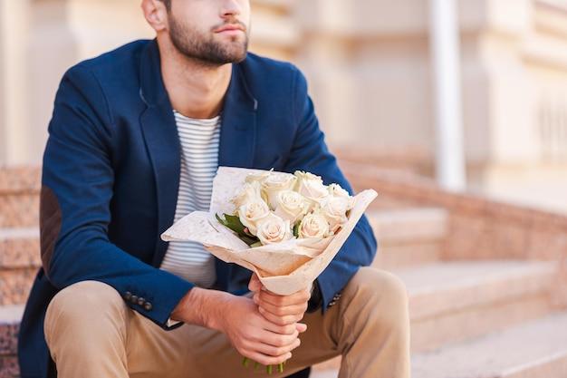 彼のガールフレンドを待っています。花の花束を保持し、家の近くの階段に座っている間スマートジャケットでハンサムな若い男のクローズアップ