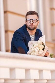 彼のガールフレンドを待っています。花の花束を保持し、屋外に立っている間目をそらすスマートジャケットのハンサムな若い男