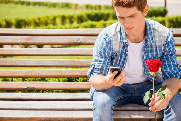 Жду свою девушку. обеспокоенный молодой человек, держащий одну розу и смотрящий на свой мобильный телефон, сидя на скамейке