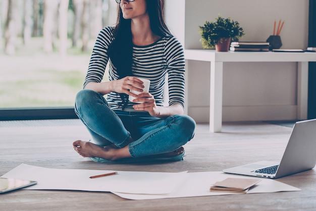 영감을 기다리고 있습니다. 커피 컵을 들고 집에서 바닥에 앉아 청사진을 옆에 두고 웃고 있는 자신감 있는 젊은 아름다운 여성의 클로즈업