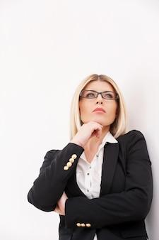 영감을 기다리고 있습니다. 턱에 손을 잡고 멀리보고 자신감 성숙한 사업가의 낮은 각도보기