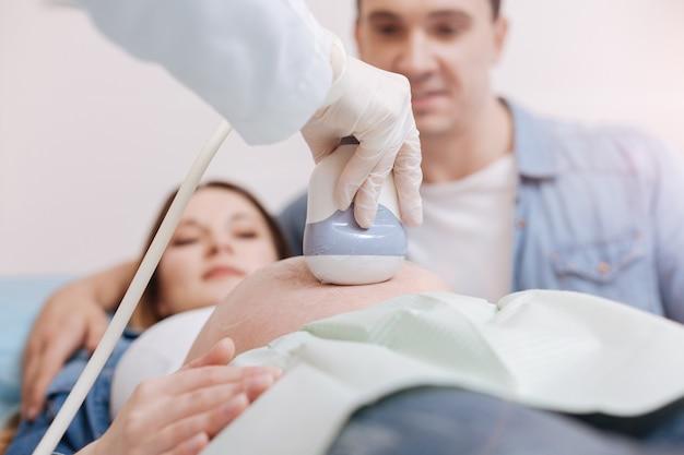 夫と一緒に新生児を待っています。病院での予約を楽しんで、超音波装置を使用して開業医が妊娠中の腹の超音波モニタリングをしている若い幸せな喜びのカップル