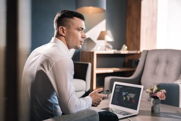パートナーを待っています。ビジネスパートナーを待っている彼のオフィスに座っている若い成功したビジネスマン