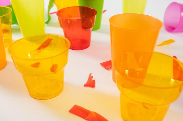 재활용을 기다리고 있습니다. 위험한 플라스틱 재질로 만든 오렌지색 투명 컵은 비 체계적인 소비를 기념합니다.