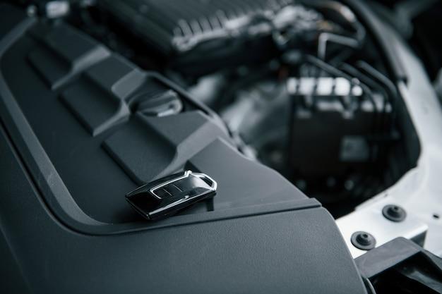 クライアントを待っています。修理は完了です。自動車のボンネットの下に寄りかかる黒い鍵