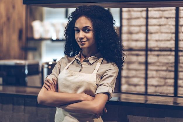 Жду первого покупателя. молодая веселая африканская женщина в фартуке, скрестив руки и глядя в камеру с улыбкой, стоя у барной стойки