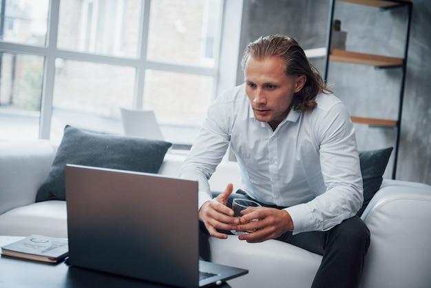 Жду сообщения. молодой человек сидит перед ноутбуком и пьет виски