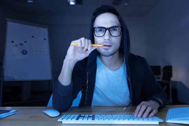 결과를 기다리고 있습니다. 컴퓨터 화면 앞에 앉아 웹 사이트에 침입하는 동안 그의 연필을 물고 잘 생긴 사려 깊은 남성 해커