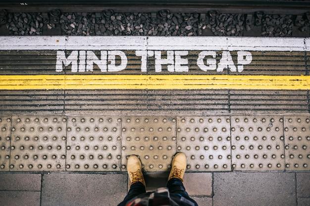 В ожидании поезда метро на станции от платформы, видя буквы mind the gap
