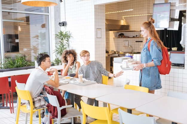 Ждем вас. эмоциональные ученики сидят за столом во время обеда в столовой