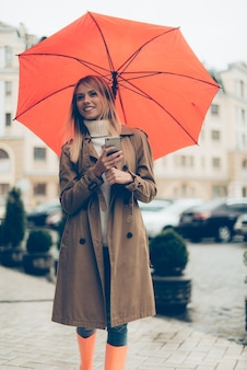 Waiting for friend. attractive young smiling woman carrying umbrella and and mobile phone while standing on the street