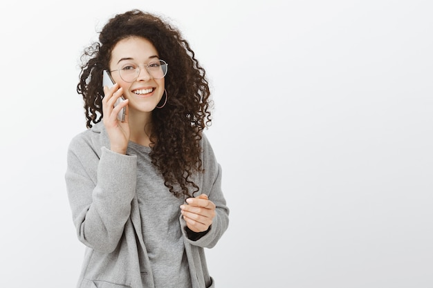 Waiting friend to pick up phone. confident beautiful curly-haired girl in fashionable coat and glasses, holding smartphone near ear and talking