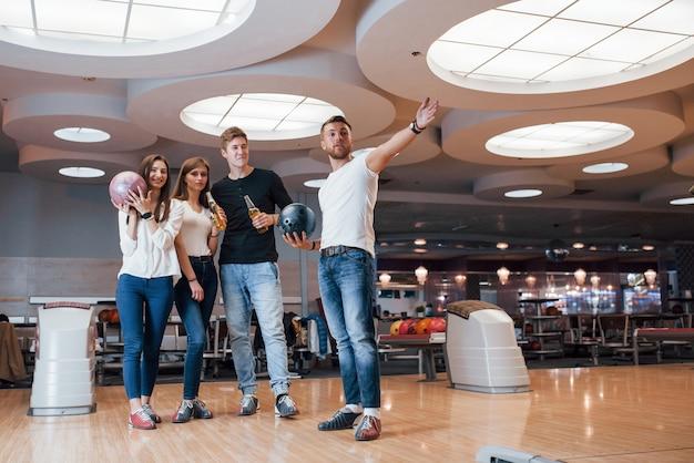 Aspettando l'inizio del gioco. i giovani amici allegri si divertono al bowling durante i fine settimana