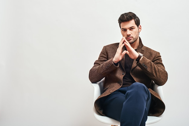 Waiting for interview stylish darkhaired man sitting on a chair crossing his legs and looking