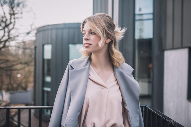 待って、会議。横を探して通りに立っているビジネス灰色のジャケットの若いきれいなブロンドの女性