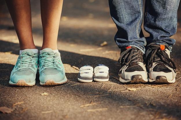 아기를 기다리고 있습니다. 아버지와 어머니의 발 근처에 작은 옷, 운동화.