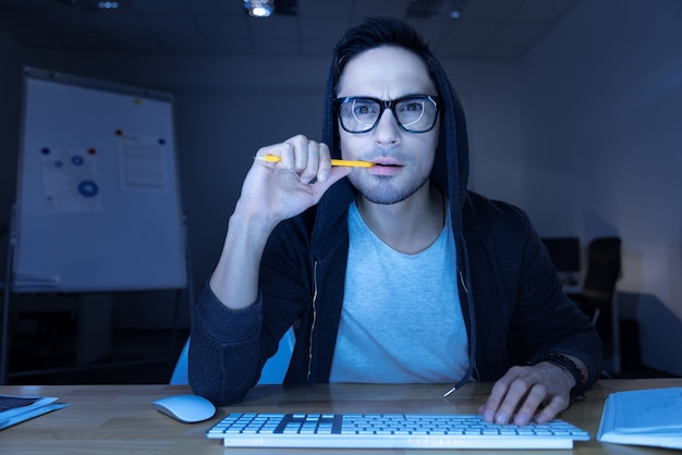 Waiting for the result. handsome thoughtful male hacker sitting in front of the computer screen and biting his pencil while breaking into a website