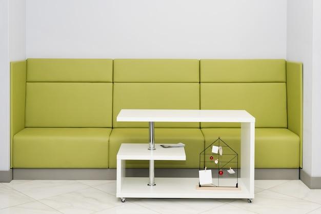 Приемная для клиентов с зеленым диваном и белым столом. современный зал ожидания кабинета врача с местом для текста