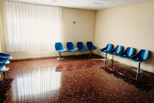 Waiting room in a hospital with empty chairs.