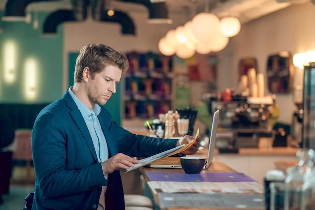 대기 중. 밝은 카페에서 노트북과 커피 앞에 앉아 있는 동안 폴더에 있는 문서를 읽는 비즈니스 정장을 입은 진지한 청년