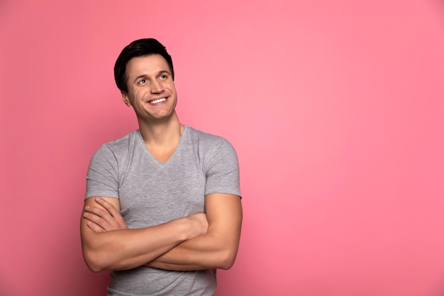Waiting for success. happy strong man in casual clothes, who is looking to the right upper corner and smiling, while standing with folded arms.