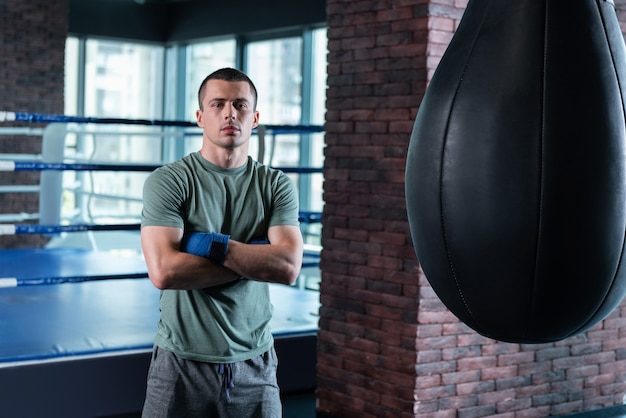 Waiting for trainer. good-looking fighter waiting for his trainer in gym while standing near big black punching bag